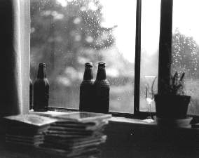 Black and white. Root beer bottles on the windowsill.  Rain-spotted window.  Some CDs piled up.